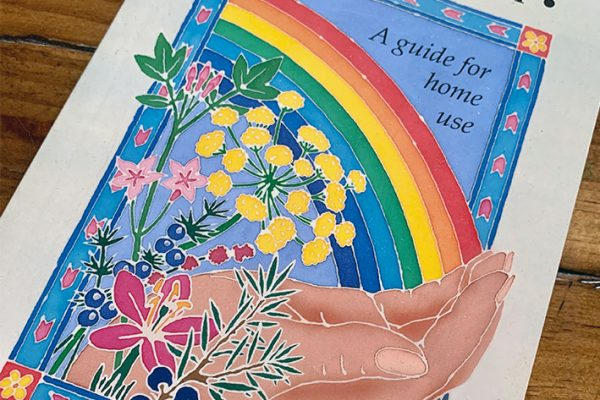 Book with hand rainbow and aromatherapy essential oils