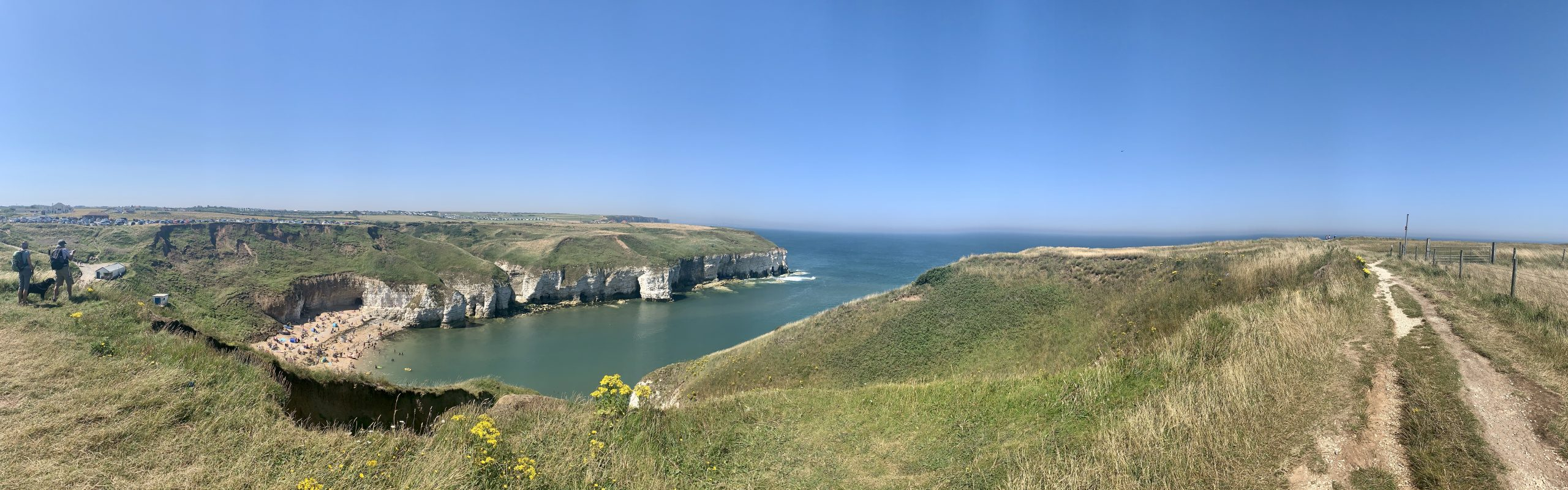 Panoramic view of Flamborough Head cliffs, blue sea with blue sky and green grass